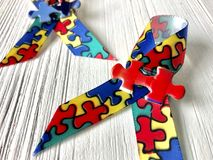 Autism awareness ribbons. Two autism awareness ribbons on a white wood background royalty free stock image