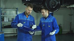 Two auto mechanic in blue uniform preparing the car for full diagnostics. Two auto mechanic diagnose car stock video
