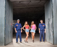 Two auto mechanic man and two beautiful girls royalty free stock image