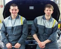 Two auto mechanics examining car with open hood. Two happy auto mechanics examining car with open hood Stock Image