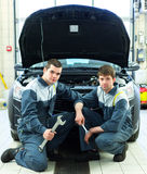 Two auto mechanics examining car with open hood. Two happy auto mechanics examining car with open hood Stock Photos