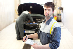 Two auto mechanics examining car with open hood Royalty Free Stock Image