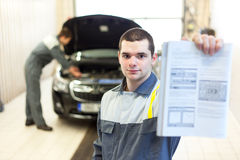 Two auto mechanics examining car with open hood Stock Image