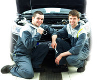 Two auto mechanics examining car with open hood. Two happy auto mechanics examining car with open hood Stock Image