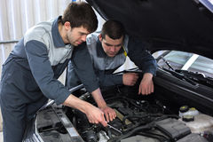 Two auto mechanics examining car with open hood. Two happy auto mechanics examining car with open hood Stock Images