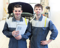 Two auto mechanics examining car with open hood. Two happy auto mechanics examining car with open hood Stock Photo
