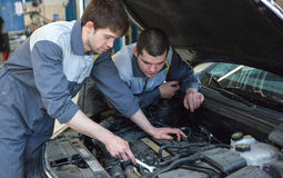 Two auto mechanics examining car with open hood. Two happy auto mechanics examining car with open hood Royalty Free Stock Photos