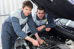 Two auto mechanics examining car with open hood. Two happy auto mechanics examining car with open hood Royalty Free Stock Photography