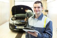 Two auto mechanics examining car with open hood Stock Photos