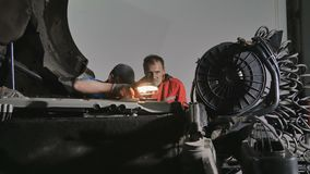 Two auto mechanics with lamp seeks the breaking of engine of truck. Two auto mechanics repairs motor of truck at car service station. The man holds a lamp and stock video footage