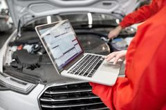 Auto mechanics doing diagnostics with laptop. Two auto mechanics in red uniform doing engine diagnostics with computer in the car service stock image