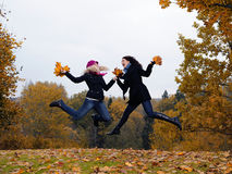 Two autumn girl friends in a park jumping Royalty Free Stock Photography