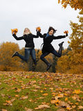 Two autumn girl friends in a park jumping Royalty Free Stock Photo