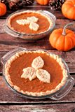Two autumn pumpkin pies with leaf pastry toppings, still life. With rustic wood background Stock Images