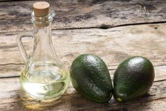 Two Avocado with Bottle of Oil on Grunge Wood Background Royalty Free Stock Photography