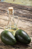 Two Avocado with Bottle of Oil on Wood Background Royalty Free Stock Photography