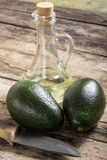 Two avocado with Knife and Bottle of Oil on Wood Background Stock Photos
