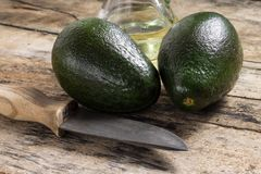 Two avocado with Knife and Bottle of Oil on Wood Background Royalty Free Stock Image