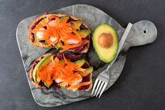 Avocado toast with beet hummus, radishes and carrots on marble server. Two avocado toasts with beet hummus, radishes and carrots on a marble server Royalty Free Stock Image