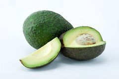 Two avocados, one is complete and the other is cut. Fresh avocados, ready for salads royalty free stock photo