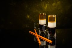 Two B-52 cocktails shot with straws on black mirror surface and dark wall background stock photo