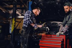 Two b mechanics working with an angle grinder in a garage. Two bearded tattooed mechanics working with an angle grinder near the car in a garage Royalty Free Stock Photography