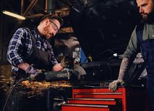 Two b mechanics working with an angle grinder in a garage. Two bearded tattooed mechanics working with an angle grinder near the car in a garage Royalty Free Stock Photos