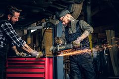 Two b mechanics working with an angle grinder in a garage. Two bearded tattooed mechanics working with an angle grinder near the car in a garage Stock Photos