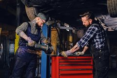 Two b mechanics working with an angle grinder in a garage. Two bearded tattooed mechanics working with an angle grinder near the car in a garage Royalty Free Stock Image