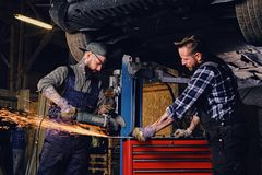 Two b mechanics working with an angle grinder in a garage. Two bearded tattooed mechanics working with an angle grinder near the car in a garage Stock Photo