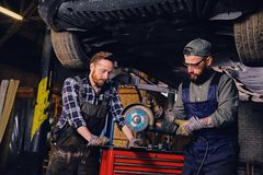 Two b mechanics working with an angle grinder in a garage. Two bearded tattooed mechanics working with an angle grinder near the car in a garage Royalty Free Stock Photo