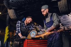 Two b mechanics working with an angle grinder in a garage. Two bearded tattooed mechanics working with an angle grinder near the car in a garage Royalty Free Stock Images