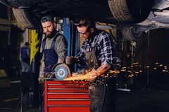 Two b mechanics working with an angle grinder in a garage. Two bearded tattooed mechanics working with an angle grinder near the car in a garage Stock Image