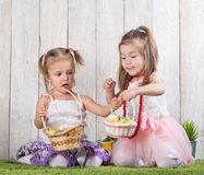 Two babes collect Easter eggs. In a basket royalty free stock photos