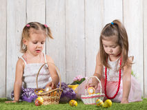 Two babes collect Easter eggs. In a basket stock photo