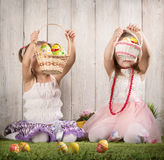 Two babes collect Easter eggs. In a basket royalty free stock photography