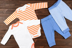 Two babies bodysuits and pants on wooden background. Baby clothe Stock Image