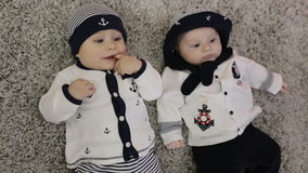Two babies boy in a sailors costumes lie next to each other. Sailors hat and jacket on children stock footage