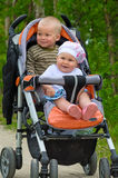 Two babies in children buggy. Two children in baby carriage. There is one year's difference of age between them. They are brother and sister Stock Photos