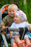 Two babies in children stroller. Two children in baby carriage. There is one year's difference of age between them. They are brother and sister Royalty Free Stock Photography