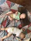 Two babies on Colorful Quilt. Two young babies play on a colorful patchwork quilt done in red, white, and blue; Summer 2018 stock image