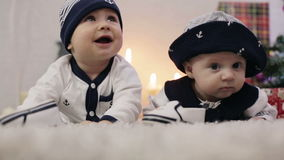 Two babies dressed as sailors lie on his stomach looking around. And laughing stock footage