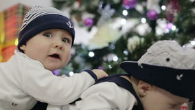 Two babies dressed as sailors lie on their stomachs and crawling near Christmas tree. Two babies dressed as sailors lie on their stomachs and crawling stock video