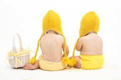 Two babies in Easter Chicken Costumes. Infant or toddler baby girl and baby boy wearing duck or chicken hats and diaper covers, studio isolated, sitting backward royalty free stock images