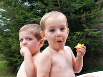 Two babies eat peach in garden Stock Photos