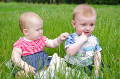 Two babies in the grass. Little boy and girl playing on a grass field stock photo