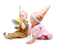 Two babies in party hats. Over white Royalty Free Stock Photography