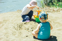 Two babies playing on beach with sand Stock Photo