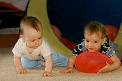 Two babies playing indoors Royalty Free Stock Photos