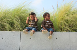 Two Babies Sitting on a Ledge. Two cute toddlers sitting on a ledge stock images